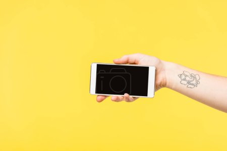 Photo for Cropped shot of person holding smartphone with blank screen isolated on yellow - Royalty Free Image