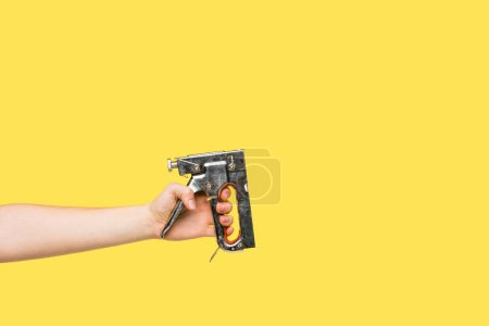 Cropped shot of person holding powered stapler isolated on yellow