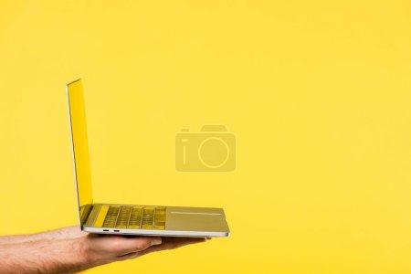 Photo pour Plan recadré de la personne tenant un ordinateur portable isolé sur jaune - image libre de droit