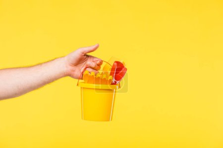 cropped shot of person holding plastic bucket with toys isolated on yellow