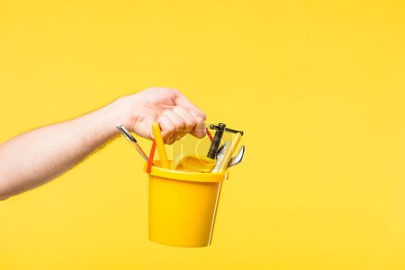 cropped shot of person holding plastic bucket with toys and tools isolated on yellow