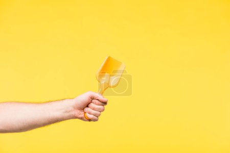 cropped shot of person holding toy shovel isolated on yellow