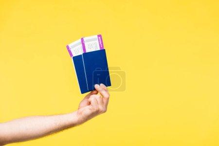Photo pour Plan recadré de la personne détenant des passeports et des cartes d'embarquement isolés sur jaune - image libre de droit