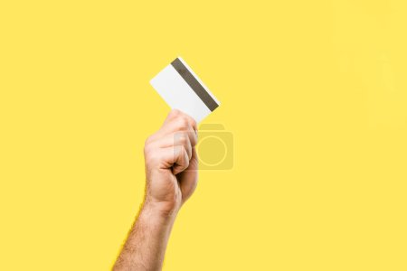 Photo for Cropped shot of person holding credit card isolated on yellow - Royalty Free Image