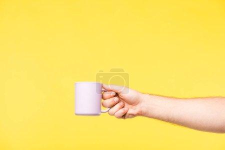 Photo pour Plan recadré de la personne tenant une tasse blanche isolée sur jaune - image libre de droit