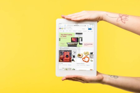 Photo for Cropped shot of person holding digital tablet with ebay website on screen isolated on yellow - Royalty Free Image
