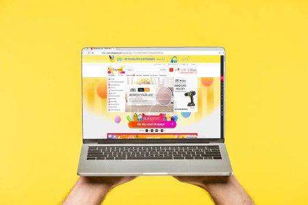 Photo for Cropped shot of person holding laptop with aliexpress website on screen isolated on yellow - Royalty Free Image