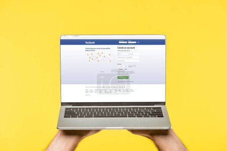 cropped shot of person holding laptop with facebook website on screen isolated on yellow