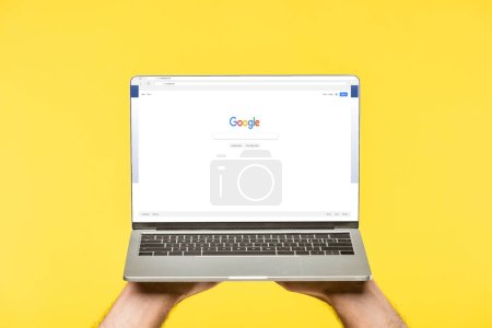 Photo for Cropped shot of person holding laptop with google website on screen isolated on yellow - Royalty Free Image