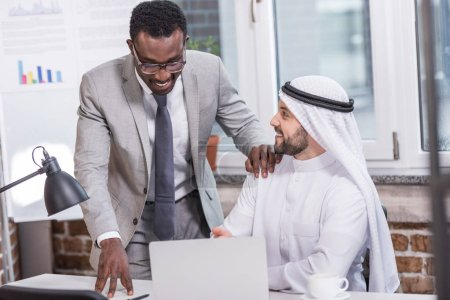 African american businessman looking at laptop and standing near arabian partner