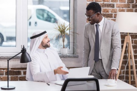 Arabian businessman talking to african american partner