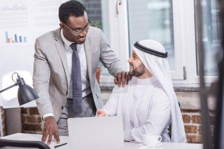 Partenaires d'affaires multiethnique parlant dans le bureau moderne