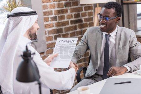 Photo pour Homme d'affaires saoudien titulaire contrat et en agitant les mains avec le partenaire américain africain - image libre de droit