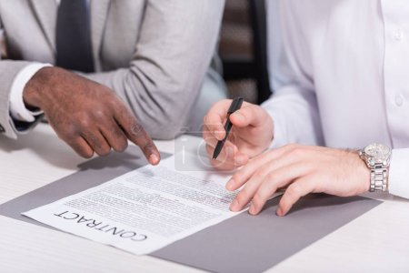 Cropped view of multicultural businessmen signing contract at office desk