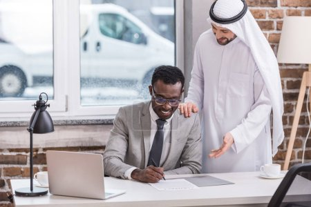 African american businessman signing contract in modern office