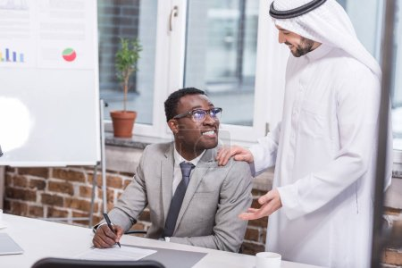 African american businessman holding pen and looking at arabian partner in office