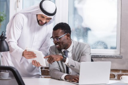 Multicultural businessmen using digital tablet in modern office