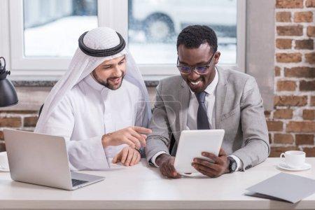 Multicultural businessmen looking at digital tablet in modern office