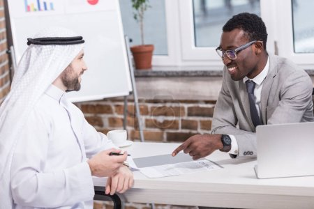 African american businessman pointing at contract while arabic partner holding pen
