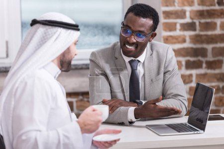 African american businessman showing laptop to arabian partner in office