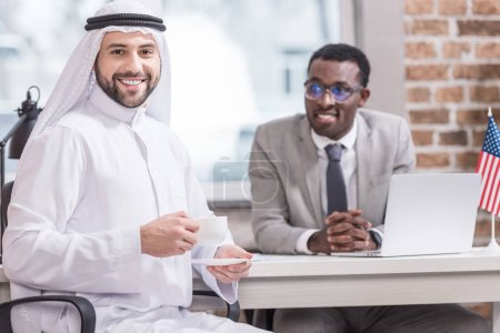 Arabian businessman drinking coffee with african american partner on background