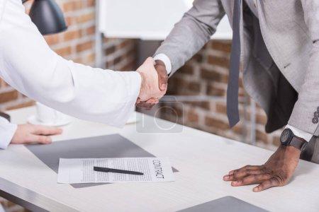Photo pour Des hommes d'affaires multiethniques se serrent la main avant de signer un contrat en fonction - image libre de droit