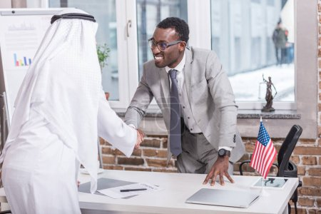 African american businessman shaking hands with arabic partner in office