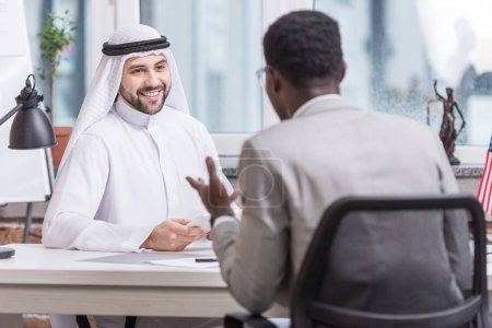 Arabian businessman sitting at desk and looking at african american partner in office