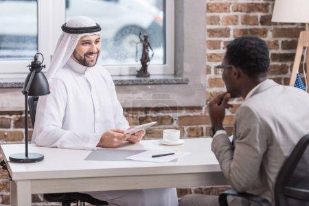 Arabian businessman holding digital tablet at office desk