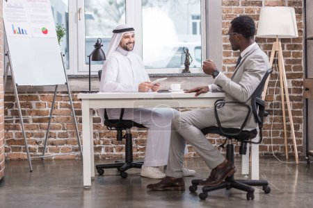 Multiethnic businessmen talking and smiling in modern office