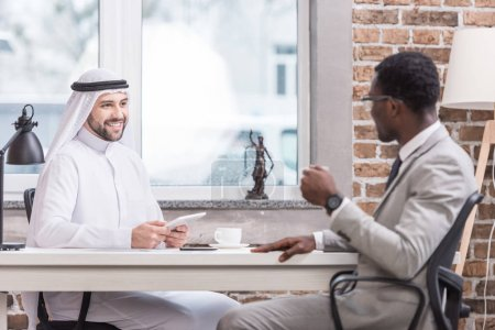 Arabian businessman holding digital tablet and having meeting with african american partner in office