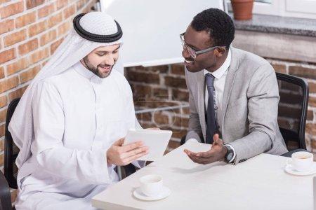 Photo pour Homme d'affaires saoudien tenant la tablette numérique et assis près de partenaire africain-américain - image libre de droit