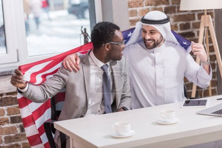 Multiethnic businessmen holding american flag in modern office