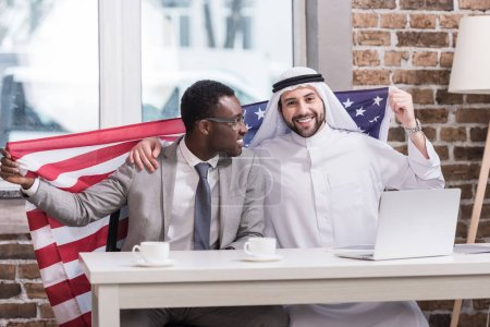 Multicultural businessmen holding american flag in modern office
