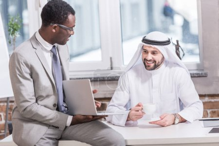 Arabian businessman looking at laptop in office