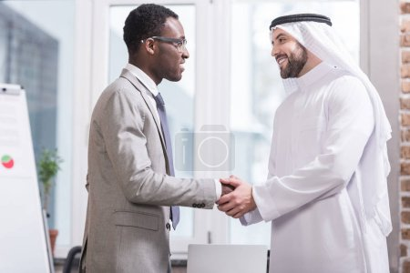 Photo pour Des hommes d'affaires multiculturels souriants et serrant la main dans un bureau moderne - image libre de droit