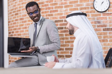 Photo pour Homme d'affaires africain-américain montrant portable arabian partenaire / au bureau - image libre de droit