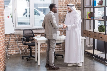 Multicultural business partners standing and shaking hands in office