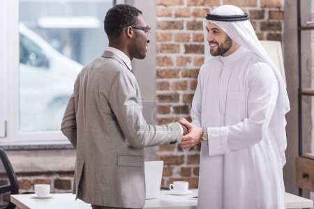 Multiethnic partners shaking hands and smiling in office