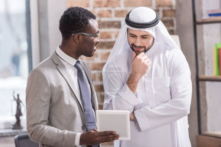 African american businessman holding digital  tablet and looking at arabian partner
