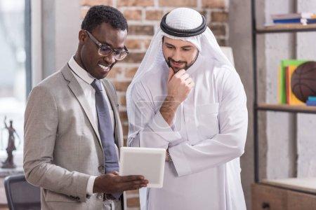 Photo pour Homme d'affaires saoudien regardant tablette numérique et pensée près de partenaire africain-américain - image libre de droit