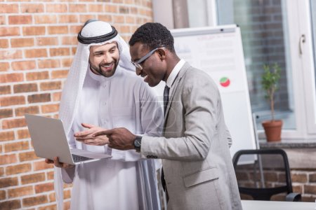 Photo for Multiethnic businessmen pointing at laptop in office - Royalty Free Image