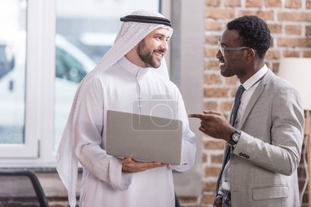 African american businessman pointing at laptop and looking on arabian partner