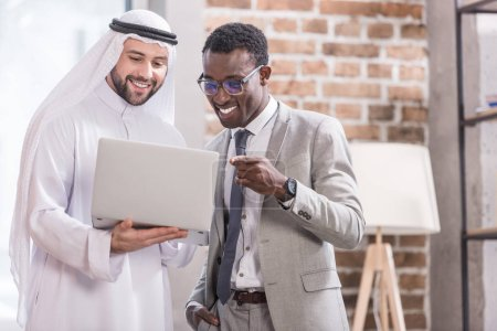 African american businessman poiniting at laptop and smiling near arabian partner