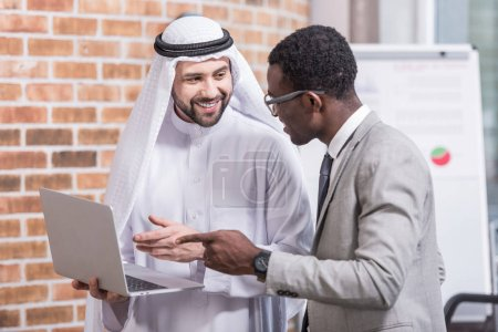 Multicultural businessmen pointing at laptop in modern office