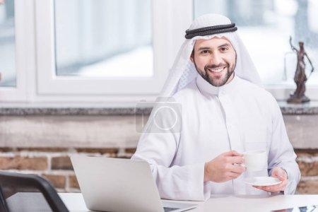 Arabian businessman drinking coffee near laptop in office