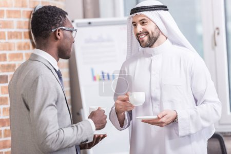 Multiethnic businessmen talking and drinking coffee in office