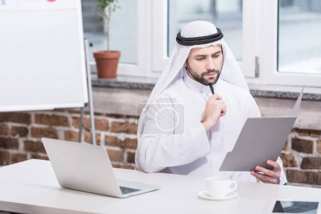 Arabian businessman looking at folder and thinking in office