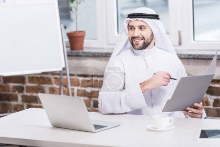 Photo pour Homme d'affaires saoudien tenant des dossier et un stylo dans le Bureau - image libre de droit