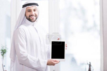 Arabian businessman showing digital tablet in office